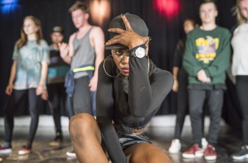 Jente med caps i forgrunnen av dansere