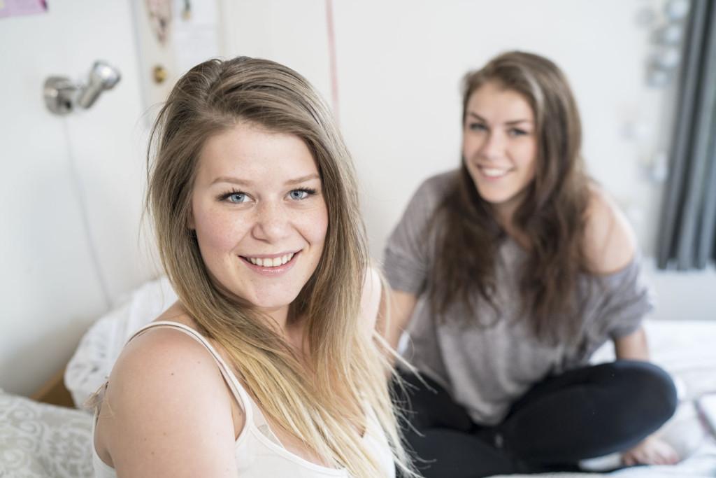 To smilende jenter som sitter i senga si