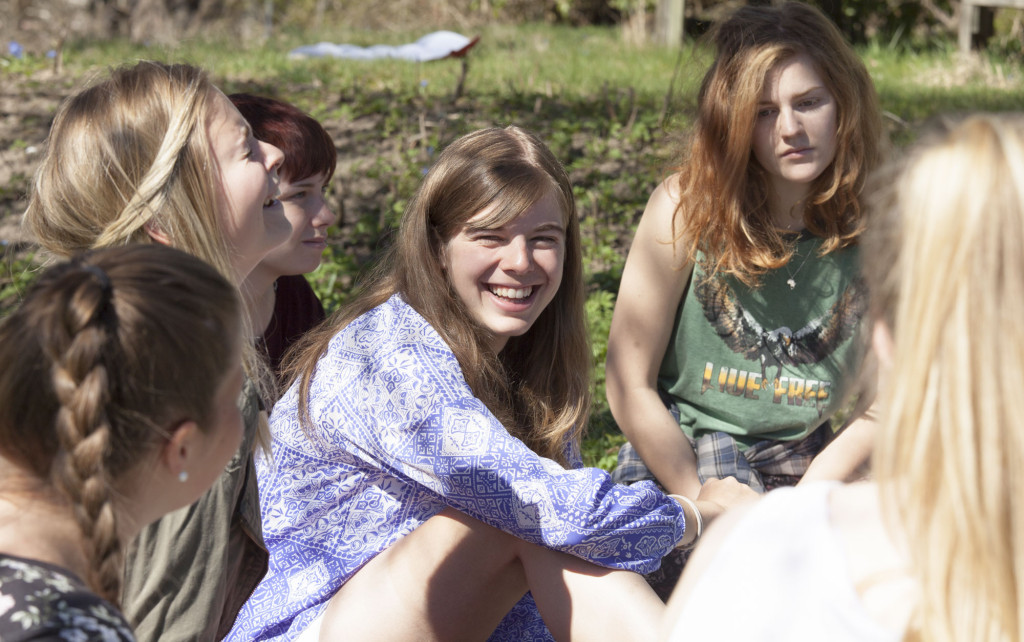 Smilende elever sitter på gresset