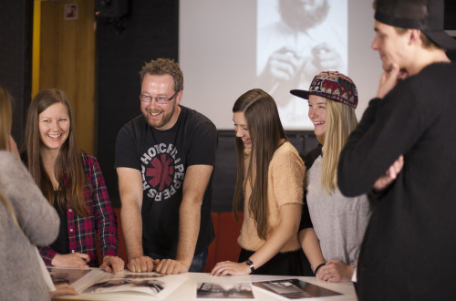 Lærer og smilende elever rundt et bord